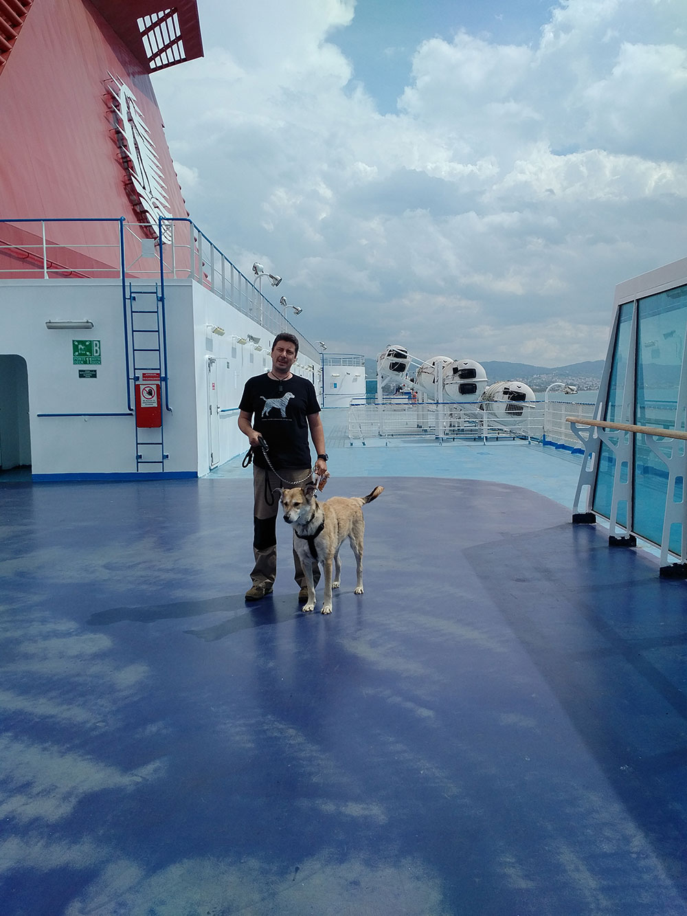 Akis on deck with Boomer, a handsome, sensitive Labrador/Alsatian cross from Athens. He's on his way to Nottingham to rejoin owner Allan.